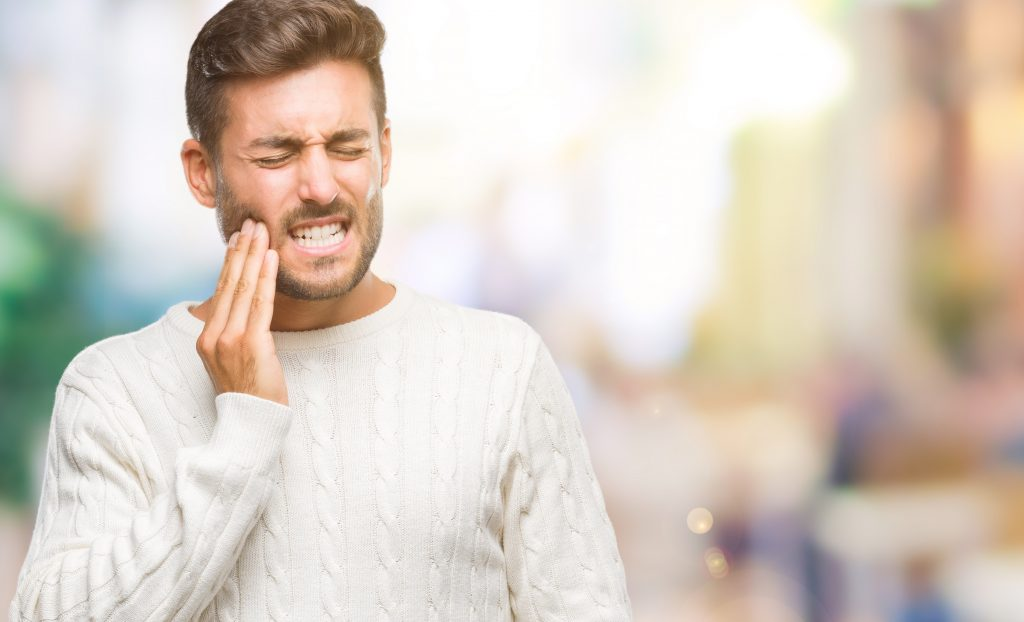 Young handsome man touching mouth with hand with painful expression because of toothache.