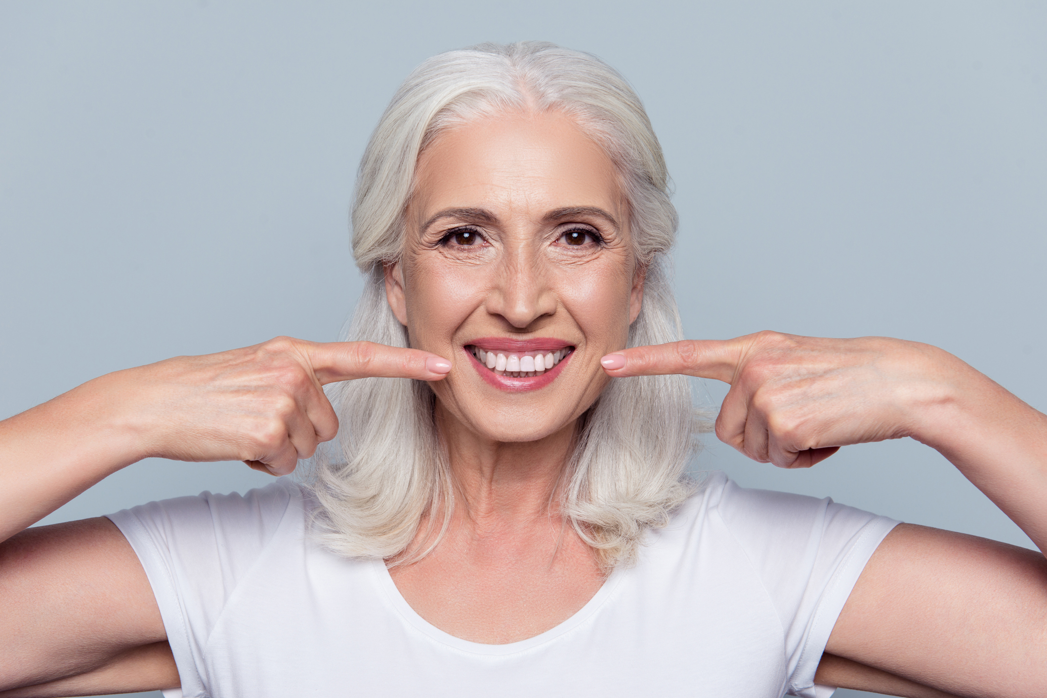 B19_Smiling-older-woman-pointing-to-both-sides-of-her-mouth