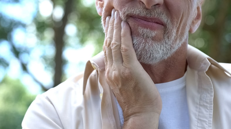 man holding his cheek periodontal therapy Orlando